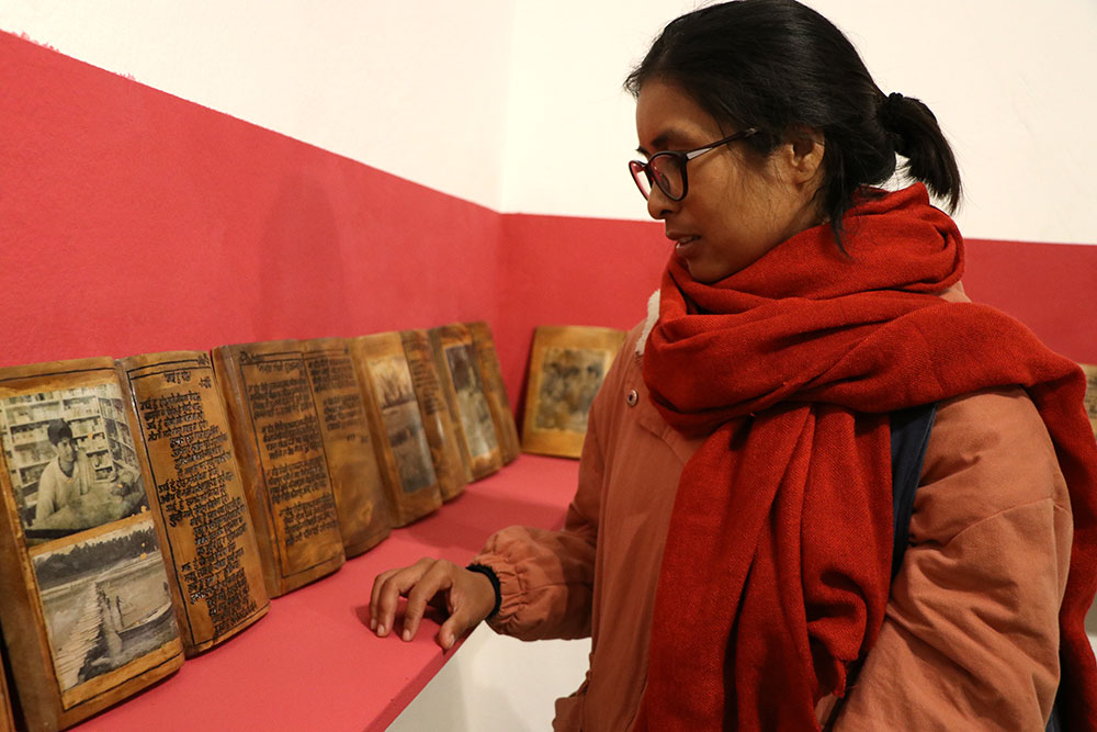 Indu looking at his father's photo in a hand-carved diary exhibited in Lavkant Chaudhary's recent solo art exhibition.