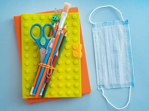 school supplies with medical face mask blue background. Protection schoolchildren students from covid-19 coronavirus, school education context pandemic.